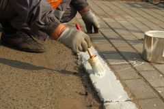 De arbeider past witte verfnoteringen op de rand toe de stedelijke dienst royalty-vrije stock afbeeldingen