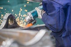 De arbeider poetst een deel van de staalbouw op - gezoem Royalty-vrije Stock Fotografie