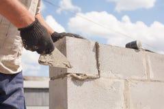 De arbeider richt zich op een spatel, legt de blokken van de baksteensintel Stock Foto's