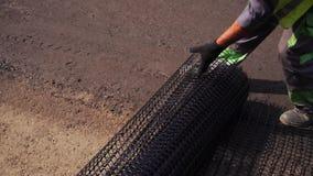 De arbeider rolt het netwerk op de weg alvorens het asfalt te leggen stock videobeelden