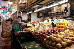 De arbeider schikt opbrengst op een plantaardige tribune bij de Markt van de Snoekenplaats Stock Afbeelding