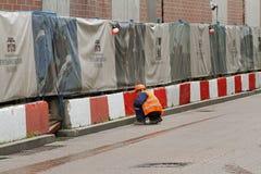 De arbeider schildert concrete blokken op de straat in Moskou Stock Foto