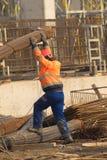 De arbeider in sinaasappel brengt de metaaldelen van de structuur over Stock Foto