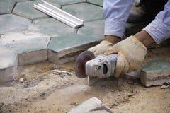 De arbeider snijdt beton voor bevloering stock afbeelding