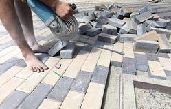 De arbeider snijdt het bedekken plakken voor het leggen op het terras Royalty-vrije Stock Fotografie