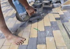 De arbeider snijdt het bedekken plakken voor het leggen op het terras op een stadsstraat bij middag royalty-vrije stock afbeelding