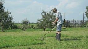 De arbeider snijdt het gras met de snoeischaar van het gazonkoord stock videobeelden