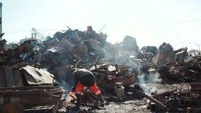 De arbeider snijdt metaal met een gassnijder op een srapyard voor recyclingsdoeleinden stock footage