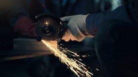 De arbeider snijdt metaal met de molen schurende zaag van de handschijf stock video