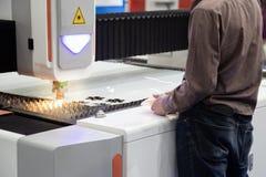 De arbeider stelt CNC lasersnijmachine in werking stock foto