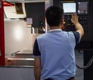 De arbeider stelt CNC machine in werking royalty-vrije stock afbeeldingen