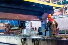 De arbeider stelt machine bij het maken van platen in werking Royalty-vrije Stock Afbeelding