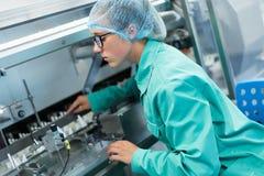 De arbeider stelt de machine bij de onderneming in werking, schone ruimte met s stock fotografie