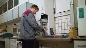 De arbeider van de achtereindmening werkt met snijmachine bij installatie stock footage
