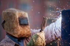 De arbeider van de booglasser in beschermende het metaalbouw van het maskerlassen Stock Foto