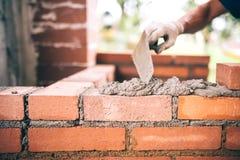 De arbeider van de bouwmetselaar de bouwmuren met bakstenen, mortier en stopverfmes Royalty-vrije Stock Afbeeldingen