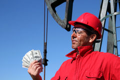 De Arbeider van de olie met de Vuile Rekeningen van de Dollar van de V.S. van de Holding van het Gezicht Stock Afbeelding