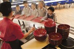 De arbeider van de schoolcafetaria dient noedels aan studenten Stock Afbeelding