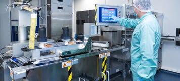 De arbeider van de de fabrieksmens van de apotheekindustrie in beschermende kleding in steriele arbeidsvoorwaarden die op geneesm stock foto's