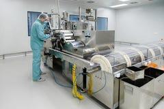 De arbeider van de de fabrieksmens van de apotheekindustrie in beschermende kleding in steriele arbeidsvoorwaarden die op geneesm royalty-vrije stock afbeelding
