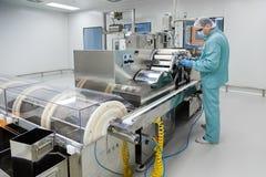 De arbeider van de de fabrieksmens van de apotheekindustrie in beschermende kleding in steriele arbeidsvoorwaarden die op geneesm stock afbeeldingen