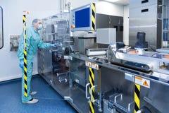 De arbeider van de de fabrieksmens van de apotheekindustrie in beschermende kleding in steriele arbeidsvoorwaarden die op geneesm royalty-vrije stock foto