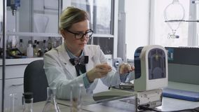 De Arbeider van het laboratoriummeisje strooit Testmateriaal in Capaciteit uit stock videobeelden