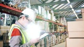 De arbeider van het portretpakhuis in een witte helm en glazen terwijl het werken stock footage