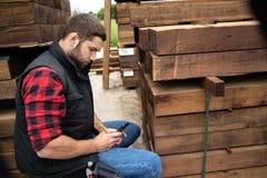 De arbeider van de timmerhoutwerf, timmerman bij houten werf telt inventaris met mobiel apparaat stock foto's