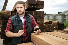 De arbeider van de timmerhoutwerf, timmerman bij houten werf telt inventaris met mobiel apparaat royalty-vrije stock fotografie