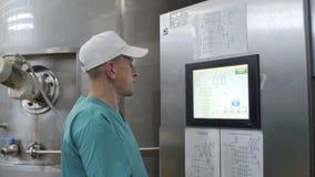 De arbeider van de voedselfabriek controleert productie bij moderne agendafabriek De mensen werken in grote winkel bij zuivelfabr stock videobeelden