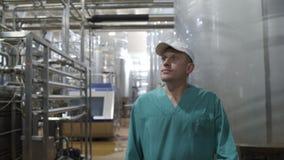 De arbeider van de voedselfabriek loopt tussen materiaal en controleert productie bij moderne agendafabriek De lijn van de melkve stock video