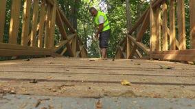 De arbeider veegde een houten brug met een borstel af stock footage