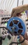 De arbeider verbetert het solderende apparaat op de borduurwerkmachine stock foto's