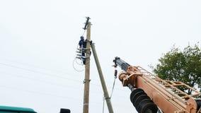De arbeider verbindt elektrodraden met lijn op pool stock footage