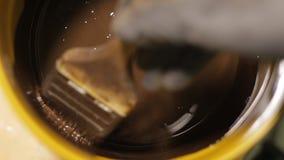 De arbeider vermindert de borstel in een bruine impregnatie voor houten, houten verf stock videobeelden