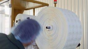 De arbeider verwijdert gebruikt document voor de verpakking van thee uit machine bij fabriek stock videobeelden