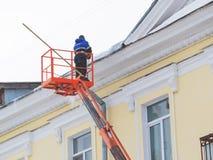 De arbeider verwijdert sneeuw en ijs uit het dak van het gebouw stock foto