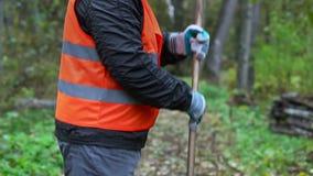 De arbeider verzamelt bladeren in het park met een hark stock videobeelden