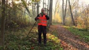 De arbeider verzamelt bladeren op gras in park in zonnig stock footage