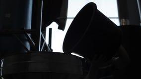 De arbeider voegt gebraden niet koffiebonen in groot aluminium om vat in koffiefabriek toe stock footage