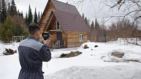 De arbeider voert een inspectie van het huis uit thermische imager Om verliezen van hitte te zoeken Strijd tegen stock video
