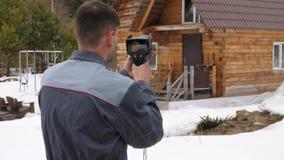 De arbeider voert een inspectie van het huis uit thermische imager Om verliezen van hitte te zoeken Strijd tegen stock footage