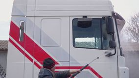 De arbeider wast de cabine van de vrachtwagen stock videobeelden