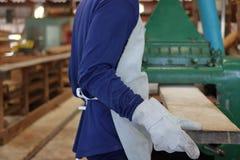 De arbeider werkt met het schaven van houten machine Hij draagt veiligheidsmateriaal in fabriek Achter mening royalty-vrije stock afbeelding