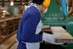 De arbeider werkt met het schaven van houten machine Hij draagt veiligheidsmateriaal in fabriek Achter mening stock afbeelding