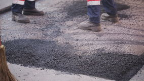De arbeiders asfalteren een beschadigde sectie van de weg stock footage