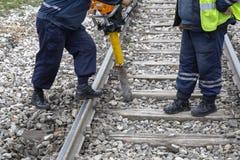 De arbeiders beginnen klemmen uit de spoorwegsporen te verwijderen stock foto's