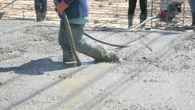 De arbeiders in bouwwerf die Trillingsmachine met behulp van voor elimineren bellen in beton stock videobeelden