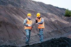 De arbeiders in bovengrondse mijnbouwverrichting maken in kuiltjes stock afbeelding
